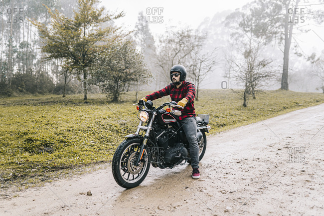 Man with motorcycle on dirt road in foggy weather