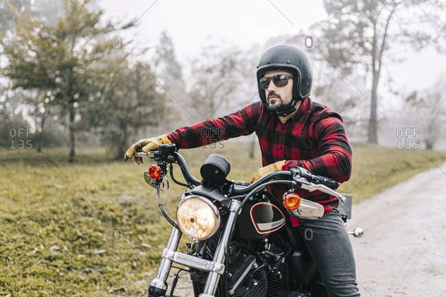 Male biker with motorcycle on dirt road in foggy weather during weekend