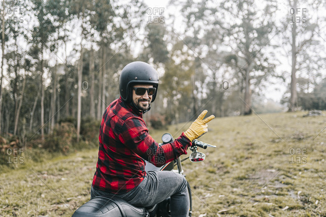 Smiling male biker gesturing while exploring forest on motorcycle