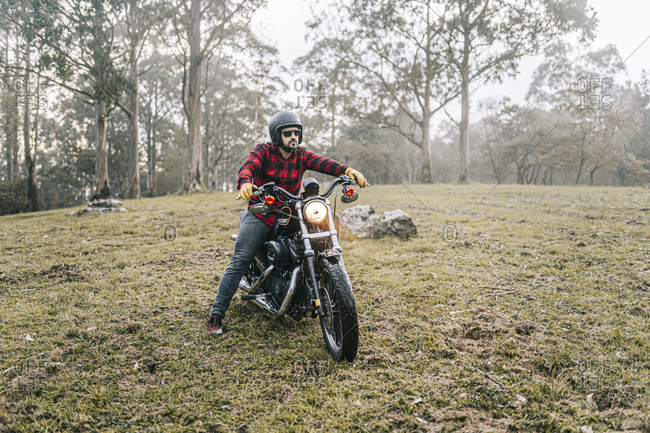 Male biker exploring forest in foggy weather