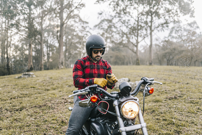 Male biker wearing gloves while sitting on motorcycle in forest
