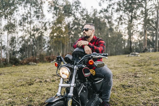 Male biker wearing sunglasses sitting on motorcycle in forest