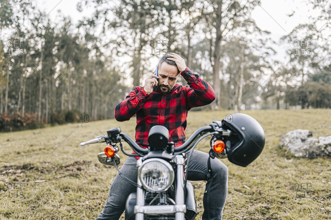 Tensed male biker talking on smart phone while sitting on motorcycle in forest
