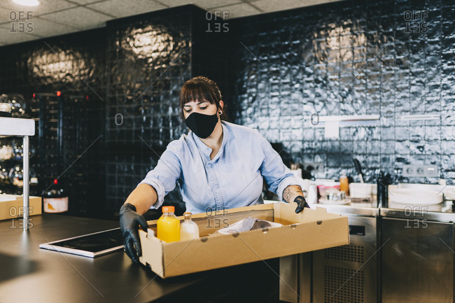 Female chef carrying cardboard box at counter in restaurant kitchen