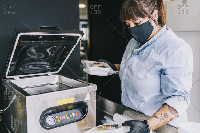 Female chef using airtight packing machinery while holding take out food at restaurant during pandemic
