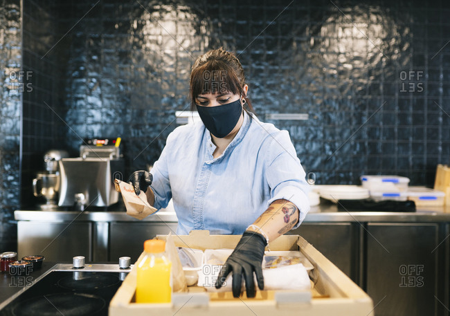 Female chef keeping take out food in cardboard box at restaurant kitchen counter during COVID-19