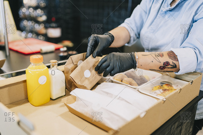 Midsection of female chef keeping take out meal packs in cardboard box at restaurant kitchen counter during coronavirus