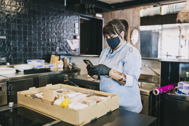 Female chef using smart phone while standing by take out food box at kitchen counter in restaurant during coronavirus