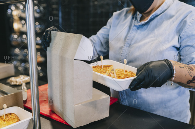 Midsection of female chef putting fresh food in cardboard box for take out at kitchen counter