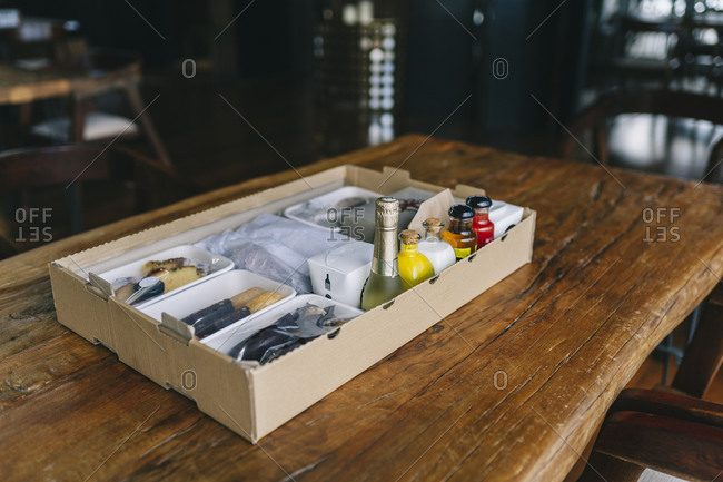 Food packages in cardboard box on wooden table at restaurant