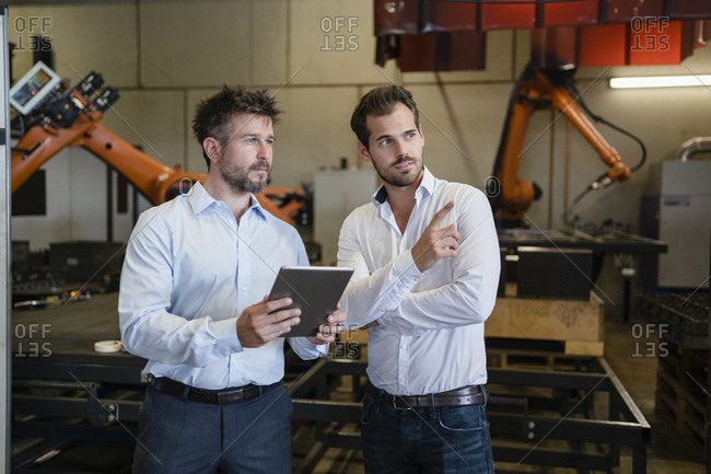 Businessman pointing while standing by colleague against automated robotic arm machine at factory