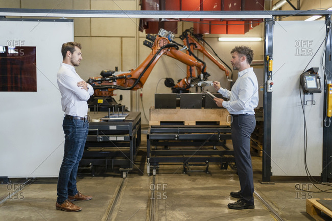 Businessman discussing with colleague while standing against robotic arm machine at factory
