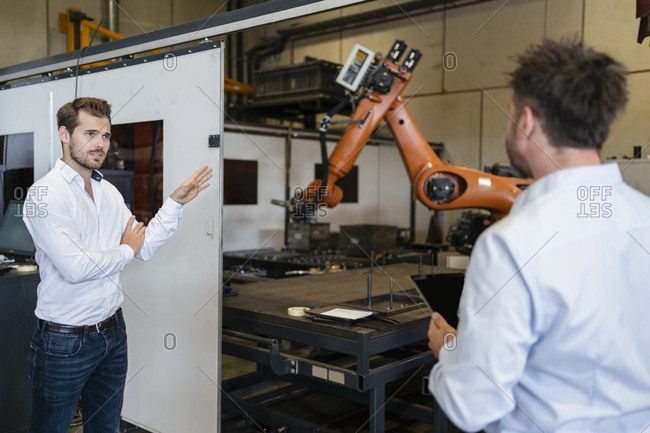 Businessman pointing at robotic arm machine while standing with colleague at factory