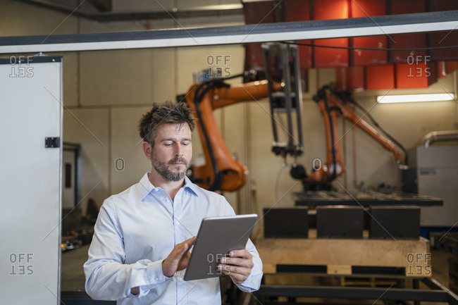 Mature businessman using digital tablet while standing against robotic arm machine at factory