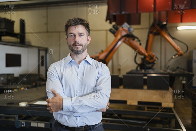 Confident mature businessman standing with arms crossed against robotic arm machine at factory