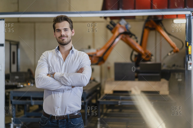 Young businessman standing with arms crossed against robotic arm at factory