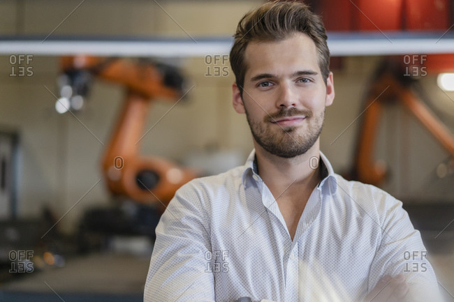 Young businessman smiling while standing against robotic arm at modern factory
