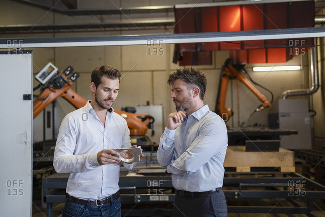 Businessman with metal object discussing with colleague while standing against robotic machine at factory