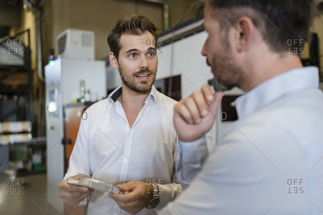 Young businessman with metal object having discussion with colleague while standing at modern factory