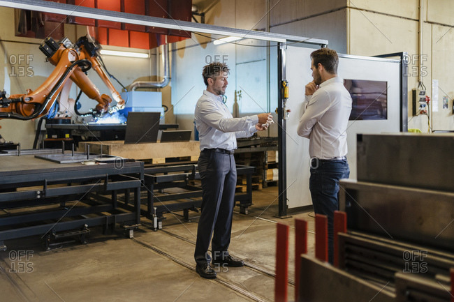 Young and mature businessman having discussion while standing against robotic machine at factory