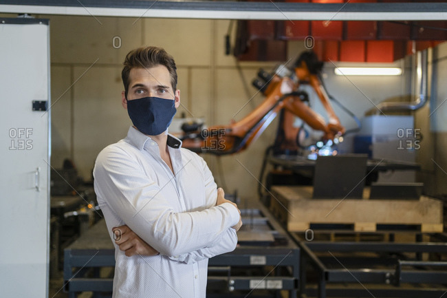 Businessman wearing face mask standing with arms crossed against robotic arm equipment at factory