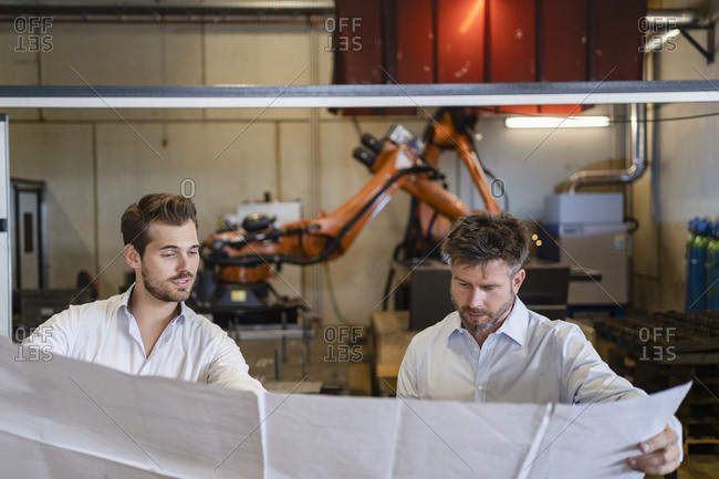 Businessmen holding blueprint paper while standing against automated machine at factory