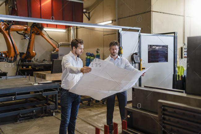 Businessmen studying blueprint of business while standing against automated machine at factory