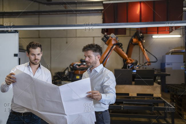 Team with blueprint having discussion while standing against robotic arm machine at factory