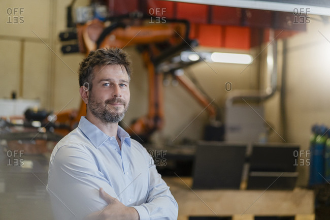 Confident businessman standing against automated robotic arm machine at factory