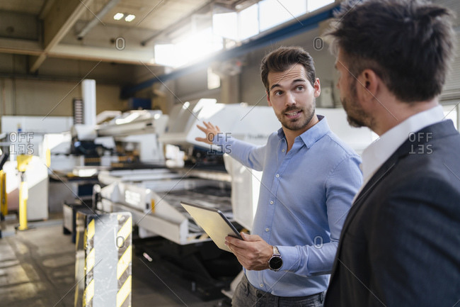 Young businessman with digital tablet gesturing toward equipment while standing by colleague at factory