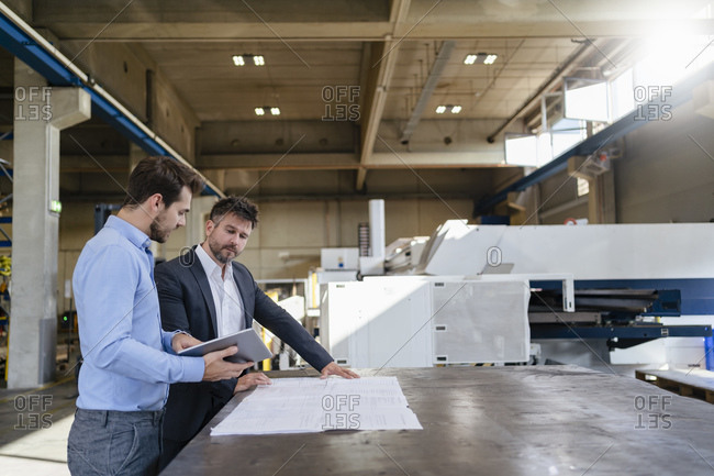 Businessmen with digital tablet and blue print standing at factory