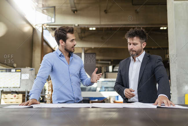 Businessmen studying blueprint while standing at factory