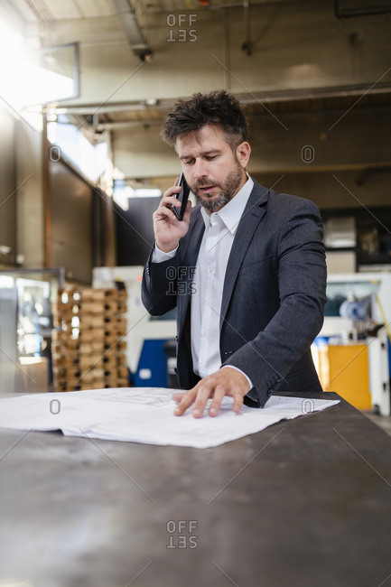 Businessman wearing suit talking on mobile phone while working at factory
