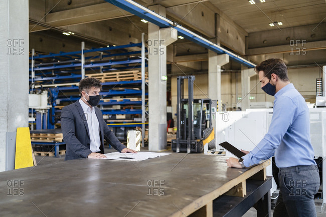 Businessman wearing face mask using digital tablet while standing at social distance with colleague in factory