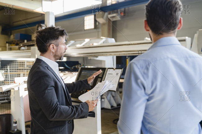 Businessman with paper having discussion with colleague while standing against machine at factory