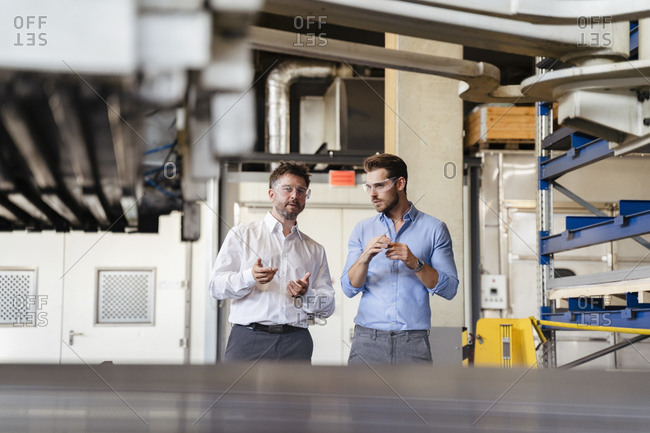 Businessmen having discussion while standing by equipment at factory