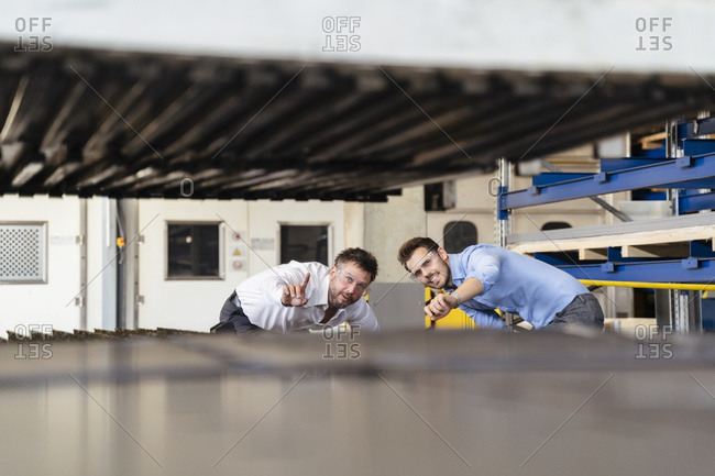Young and mature expertise examining manufacturing equipment while standing at factory