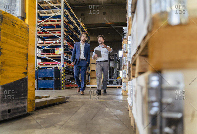 Man using digital tablet while inspecting warehouse with businessman at factory