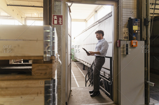 Mature man using digital tablet while standing by delivery truck at factory