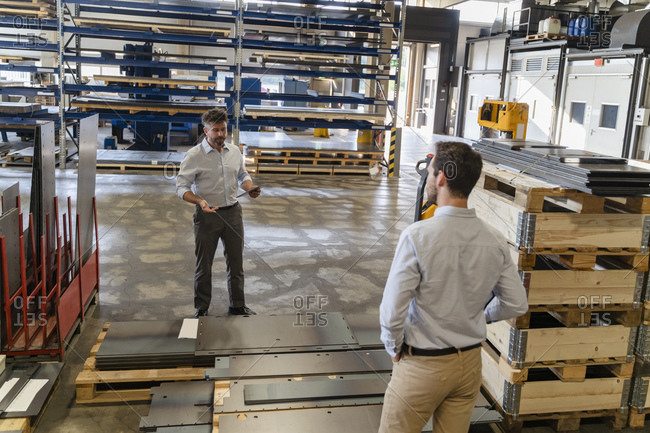 Business people standing by equipment while having discussion at factory