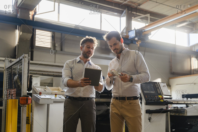 Businessmen using digital tablet while examining metal object at factory