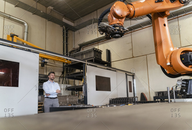 Businessman with arms crossed monitoring automatic robot arm while standing at factory
