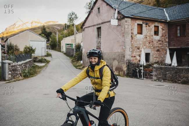 Mid adult woman in warm clothing riding mountain bike on road while traveling to Somiedo Natural Park- Spain