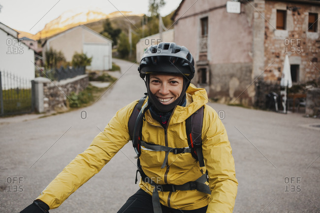 Smiling mid adult woman in warm clothing riding mountain bike on road while traveling to Somiedo Natural Park- Spain