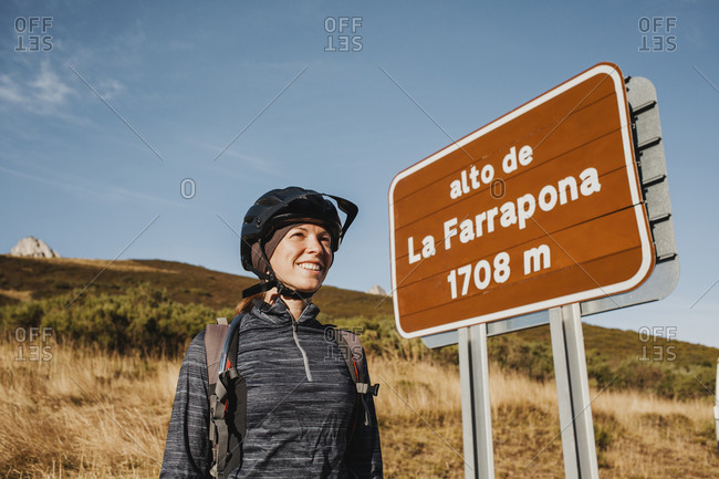 Smiling mid adult woman wearing cycling helmet standing by sign board at Somiedo Natural Park- Spain