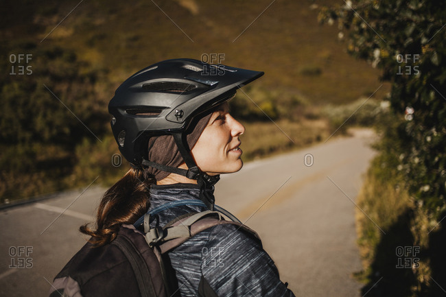 Woman wearing cycling helmet standing on mountain path at Somiedo Natural Park- Spain