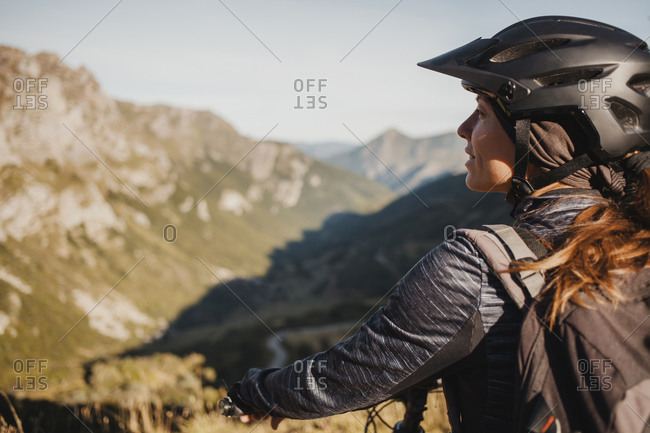 Mountain biker with bicycle standing while admiring mountain view at Somiedo Natural Park- in the north of Spain