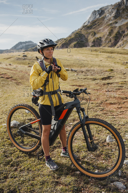 Woman in warm clothing standing on mountain bike at Somiedo Natural Park- Spain