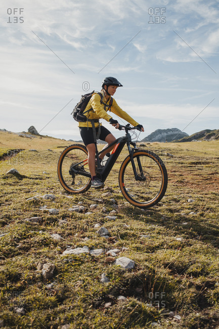 Female mountain biker riding bicycle on mountain at Somiedo Natural Park- Spain