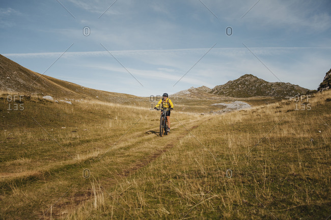 Female in warm clothing riding electric bicycle on mountain at Somiedo Natural Park- Spain